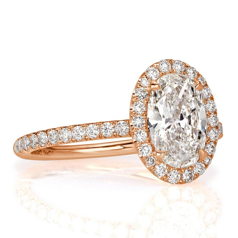 Custom created in 18k rose gold, this beautiful diamond engagement ring showcases a gorgeous 1.74ct oval cut center diamond, GIA certified at I in color, VS1 in clarity. It is has a stunning cut and sparkles with tremendous brilliance. It is