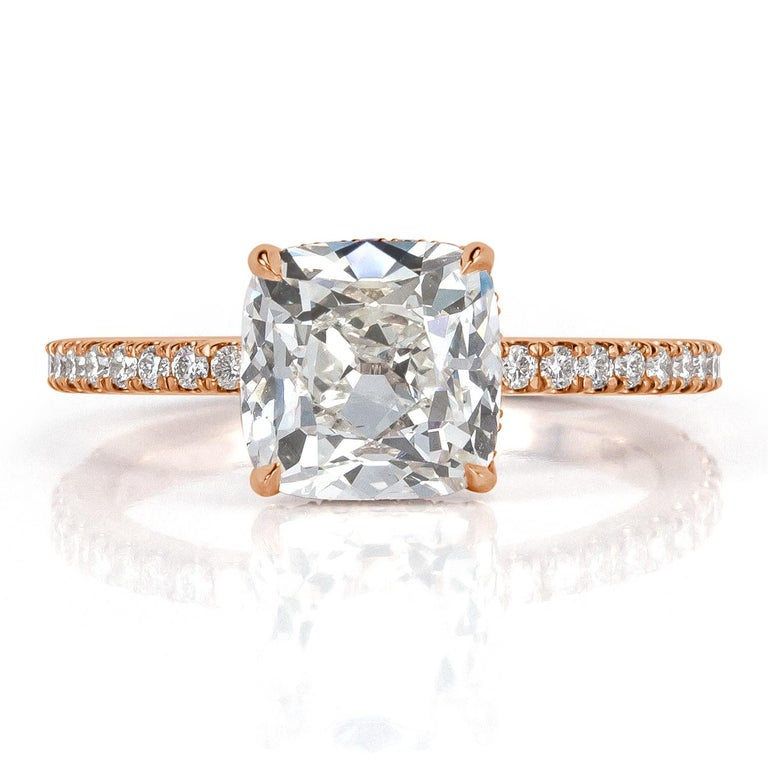 Custom created in 18k rose gold, this one of a kind cushion cut diamond engagement ring showcases a superb 2.10ct center diamond, GIA certified at I-SI2. It faces up white and is completely eye clean with amazing measurements of 8.19 x 7.46mm which