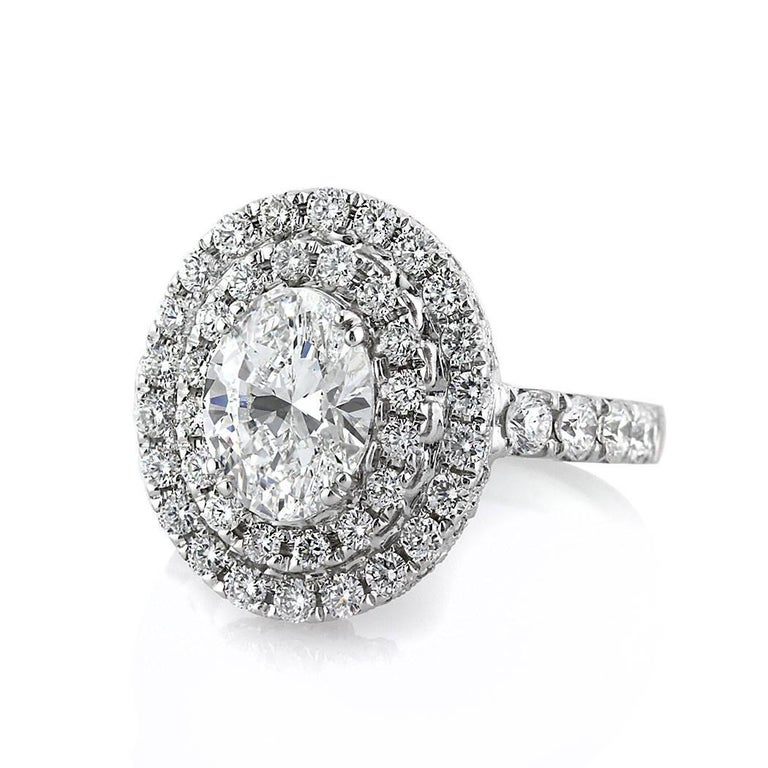 Exquisitely handcrafted in 18k white gold, this superb diamond engagement ring features a gorgeous 2.01ct oval cut center diamond, GIA certified at D-VS1. It is beautifully accented by a double halo of round brilliant cut diamonds as well as one row