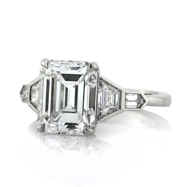 This emerald cut diamond engagement ring features an enchanting 3.74ct emerald cut center diamond GIA certified at F-VVS2. It is accented by step cut trapezoids flanked on its sides in a bezel setting and followed by a special cut bullet shape