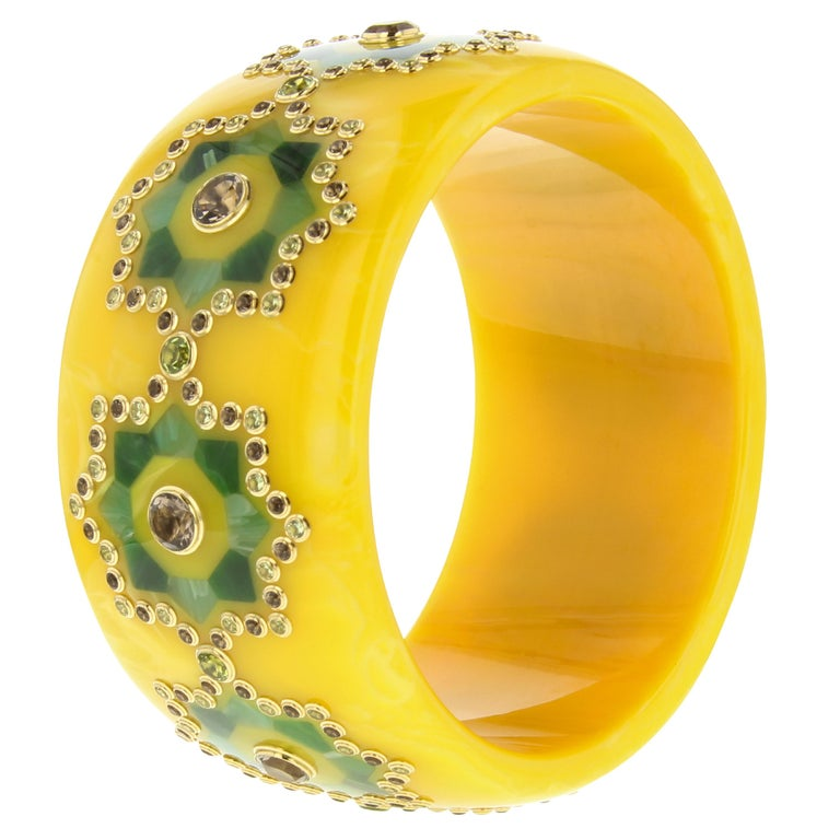 A masterpiece by Mark Davis. This bangle of vintage yellow bakelite has been inlaid with two shades of green bakelite forming a stylized girih pattern with an eight-pointed star. The center of each star is set with smoky quartz in 18k gold. An