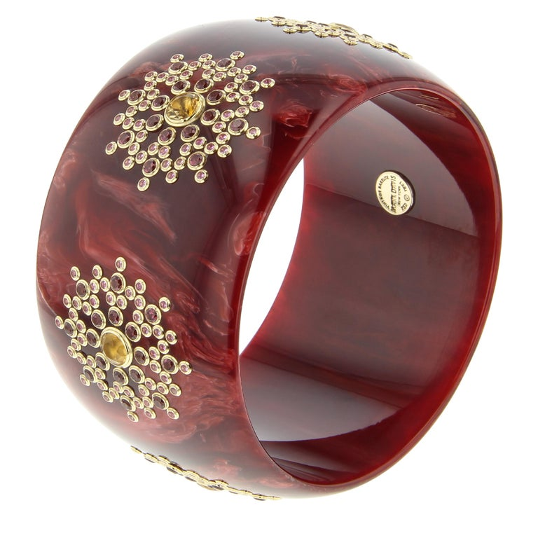 This elegant bangle was created with a rich, vintage, burgundy bakelite that has been set with fine gemstones in a complex and super-precise geometric pattern. The color of the bakelite and gemstones makes this bangle ideal for year-round wear.