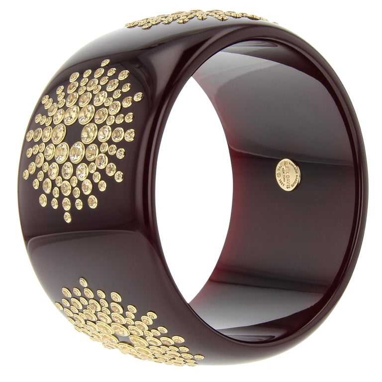 This head-turning Mark Davis bangle was made by hand using a very deep purple, unmarbled, vintage bakelite. A brilliant starburst pattern has been precisely applied to the bangle. Every stone in the pattern has been individually set in 18k yellow