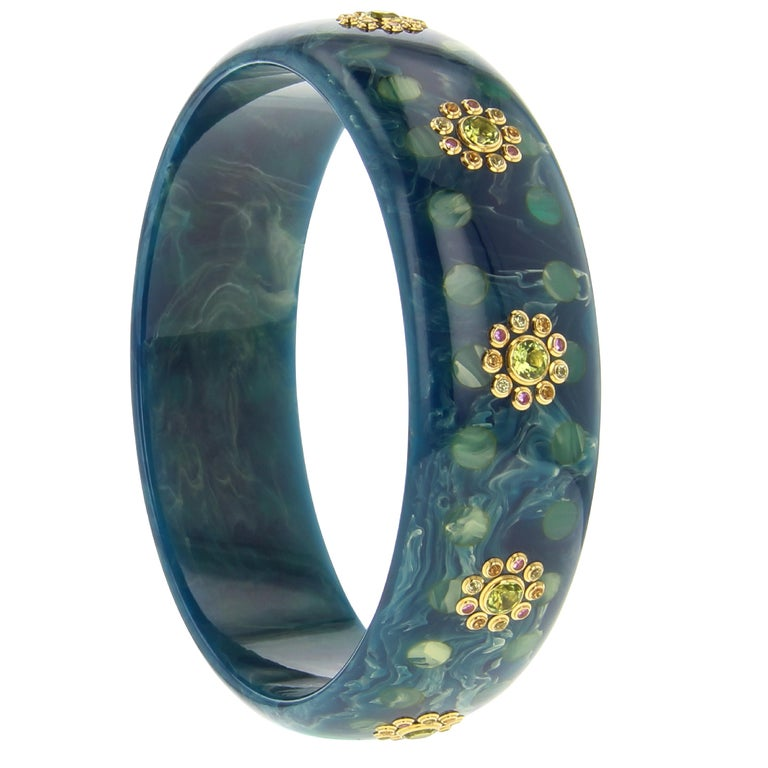 This Mark Davis bangle was made from a beautiful marbled blue bakelite inlaid with a tonal polka dot pattern. Evenly spaced clusters of gemstones circle the bangle. Each cluster is comprised of a central peridot surrounded by smaller peridot,