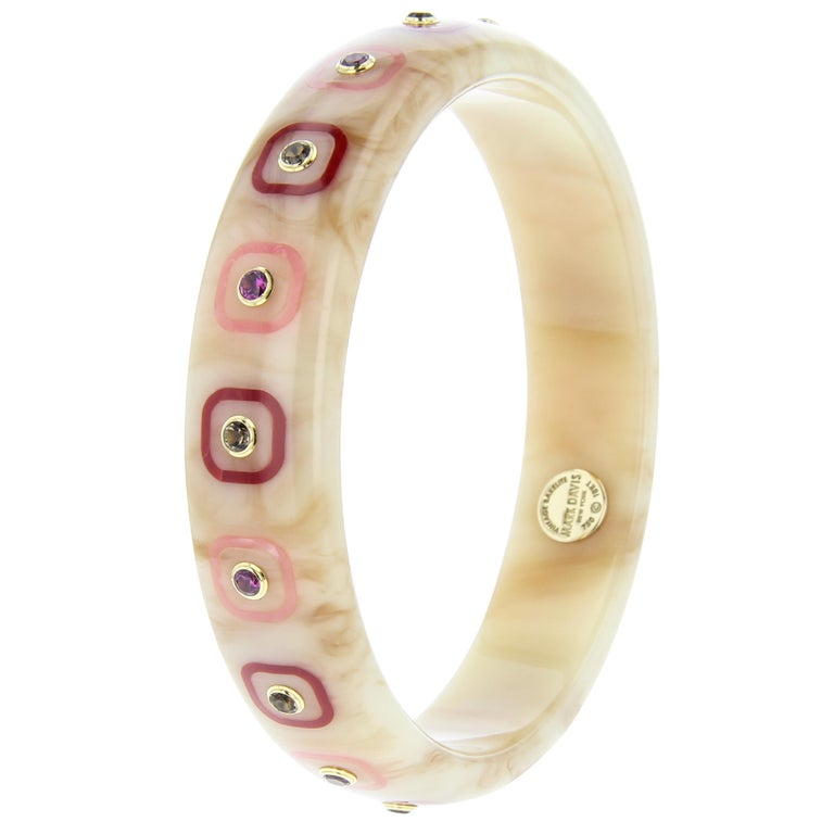 This charming and delicate bangle was created by Mark Davis using a very softly marbled, beige, vintage bakelite. The subtlety of the bakelite is contrasted with alternating burgundy and pink bakelite inlaid squares. The rounded squares are centered