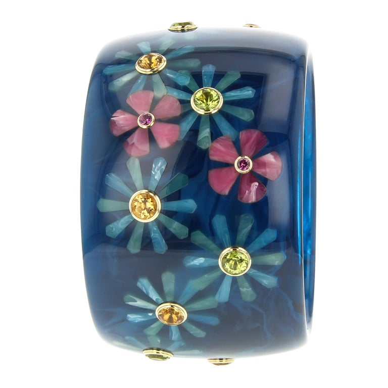 This beautiful Mark Davis bangle was created using a very subtly marbled, navy blue, vintage bakelite. A random floral pattern of greenish-blue or pink blossoms is scattered all around the bangle. The flowers are each set with a round colored