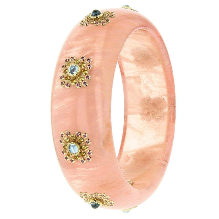 This lovely and feminine Mark Davis bangle was made with a very unusual, light pink, marbled bakelite. The bakelite shows pronounced translucency in areas that enhance the marbeling to geat effect. Nine stations created from precisely set clusters