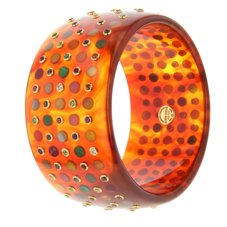 This bold and exquisite Mark Davis bangle was handcrafted using a warm, reddish, marbled tortoiseshell color vintage bakelite precisely inlaid with five rows of multi-colored bakelite polka dots alternating with various gemstones set in 18k gold
