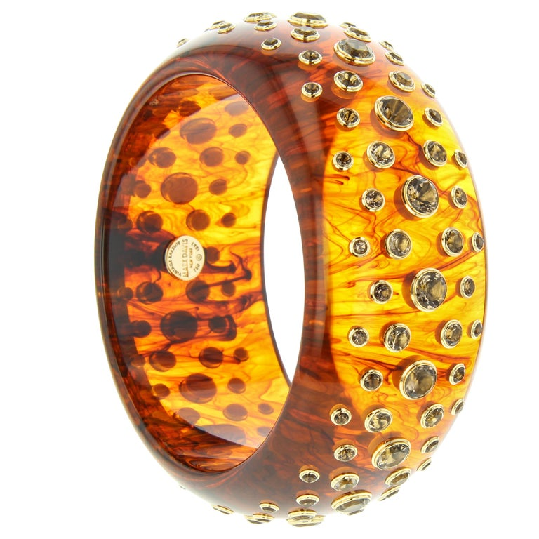 This Mark Davis bangle was handcrafted using a warm, honey-toned, tortoiseshell color vintage bakelite set with graduated smoky quartz in individual 18k yellow gold bezels.  Full details below: • From the Mark Davis Bakelite line • Vintage tortoise