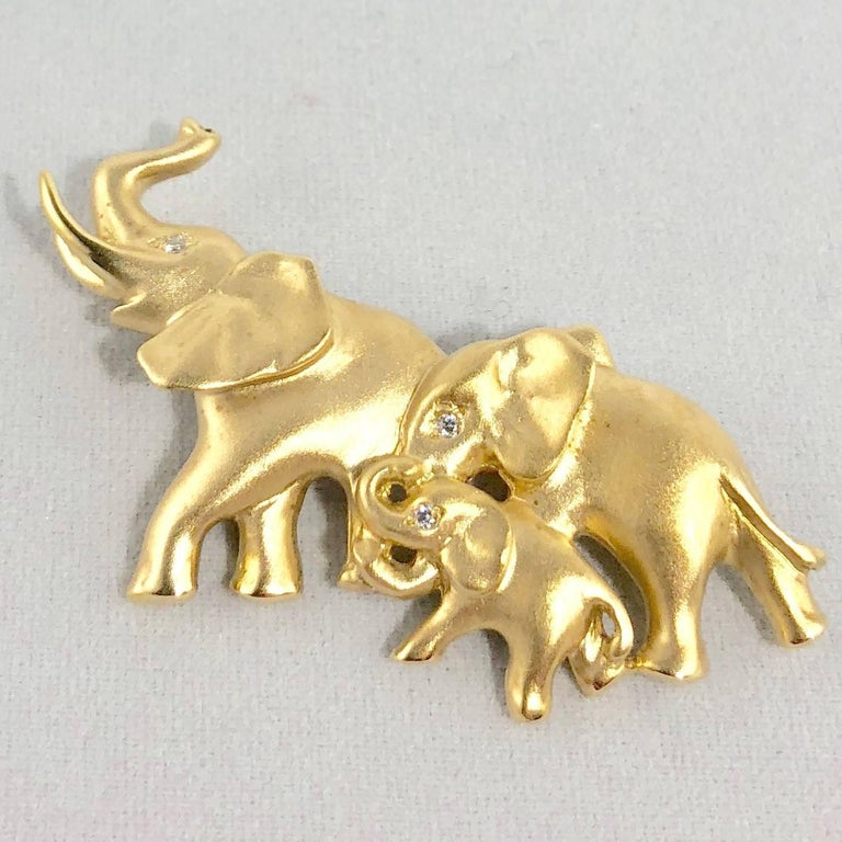 Mark Schneider 18 karat gold and diamond modern elephant brooch. This piece is created in 18 karat yellow gold and weighs 13.0 grams/ 8.3 dwt. There are 3 full cut round diamonds in this piece equaling .02 carats total weight. Color G-H, Clarity
