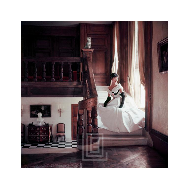 "Romance Heroine in White Satin Fath on Stairs, Wide -- Photographed in 1953 at the French country estate, Corbeville, the Irish beauty Anne Gunning poses in a ball gown by Fath. Image size is 16"" x 16"" (for 17"" x 22"" paper size). All Mark Shaw"