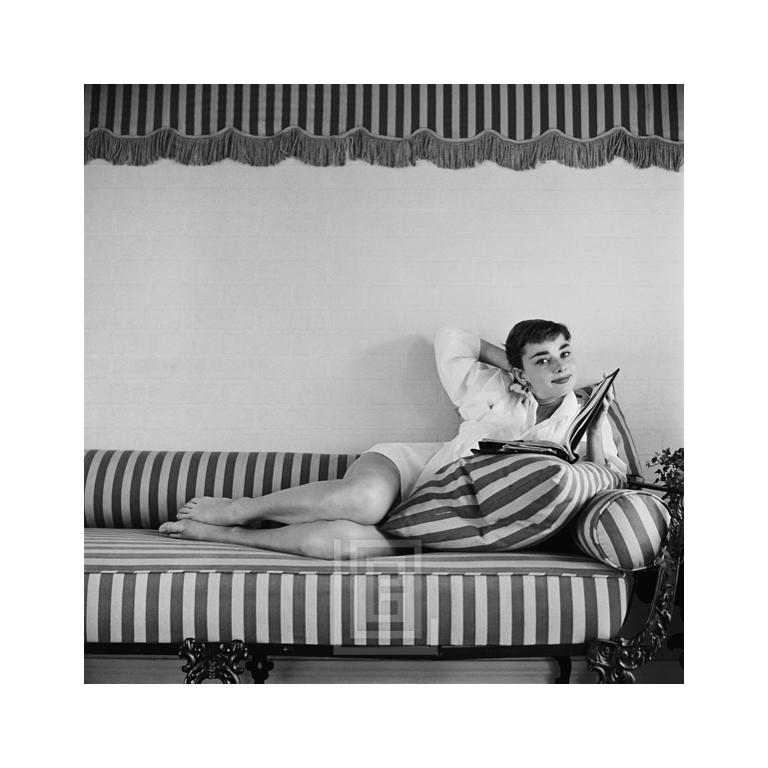 Mark Shaw Black and White Photograph - Audrey Hepburn on Striped Sofa, Arm Back, Head Tilted, 1954