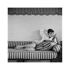 Audrey Hepburn on Striped Sofa, Arm Back, Head Tilted Smiling, 1954