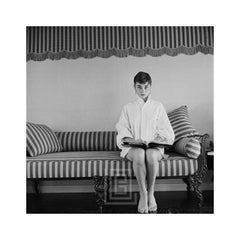 Audrey Hepburn on Striped Sofa, Faces Forward with Book Open, 1954