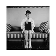 Audrey Hepburn on Striped Sofa, Hands on Closed Book, 1954