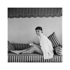 Audrey Hepburn on Striped Sofa, Leans Forward Smiling, 1954