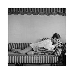 Audrey Hepburn on Striped Sofa, Rests on Book, 1954