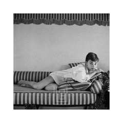 Audrey Hepburn on Striped Sofa, Rests on Book Head Up, 1954