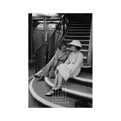 Coco Chanel Sits on Stairs with Unidentified Woman, 1957
