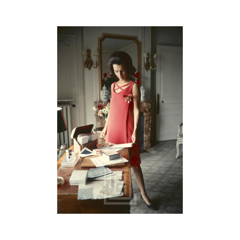 Dior, Lee Radziwill, Red Dress at Desk, 1962 - Photograph by Mark Shaw