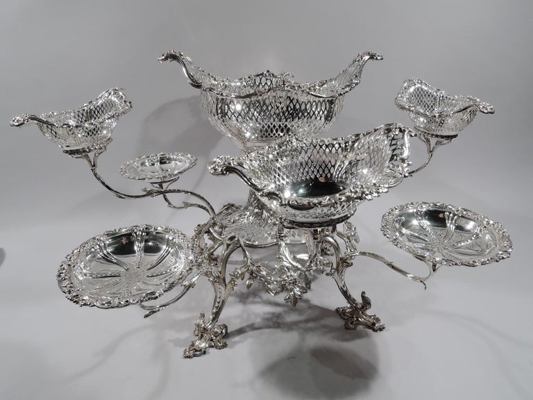 Market-fresh George III sterling silver epergne. Made by Thomas Pitts in London in 1766. Pierced and oval support set in round floral garland frame with four leafing scroll supports on same feet. Large and pierced oval basket, surrounded by