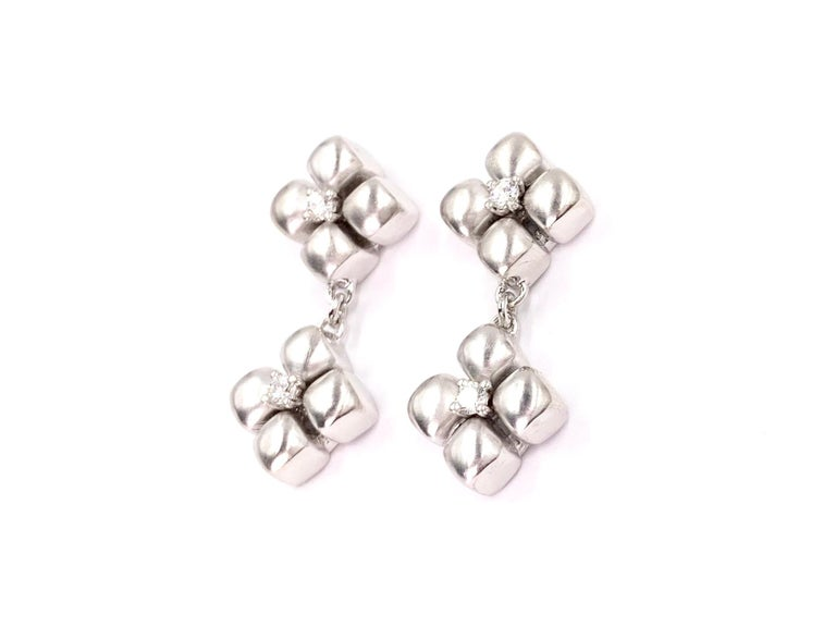Made with superior quality by Marlene Stowe. These timeless and chic floral drop earrings are made of platinum and 18 karat white gold with a round brilliant diamond set in the center of each flower for a subtle sparkle. Earrings have a diamond