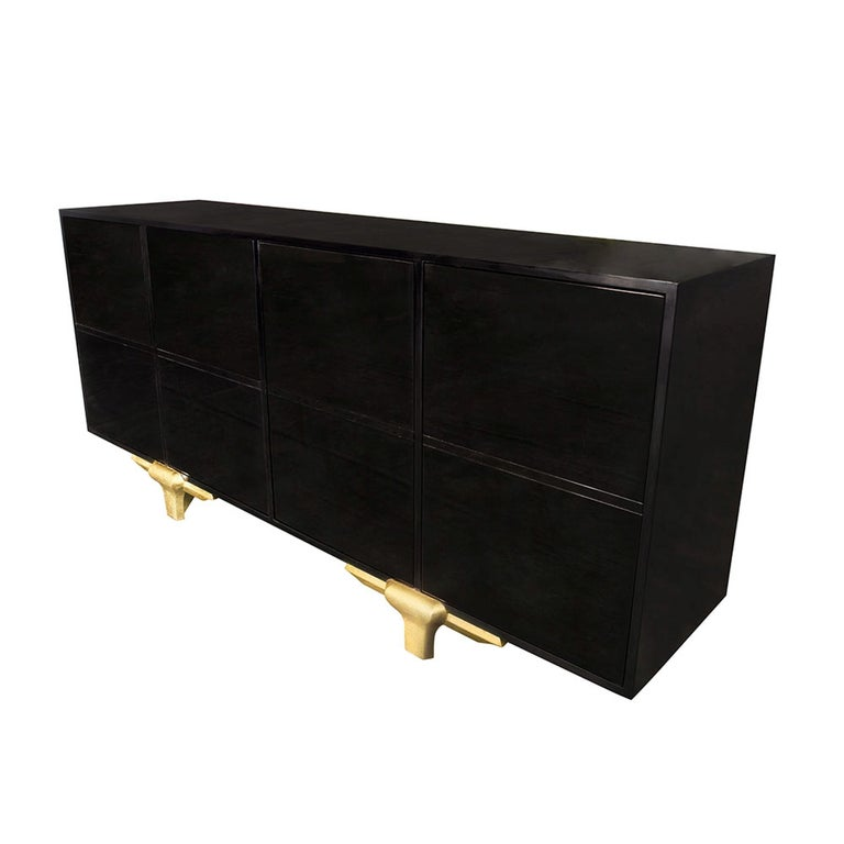 With its grand appeal, the Marmont buffet is a stunning, sophisticated piece. Its incredibly clean design makes the lacquered ebony wood look as if it is merely oating on the hand carved gold leaf legs. Every inch of this sleek design has been