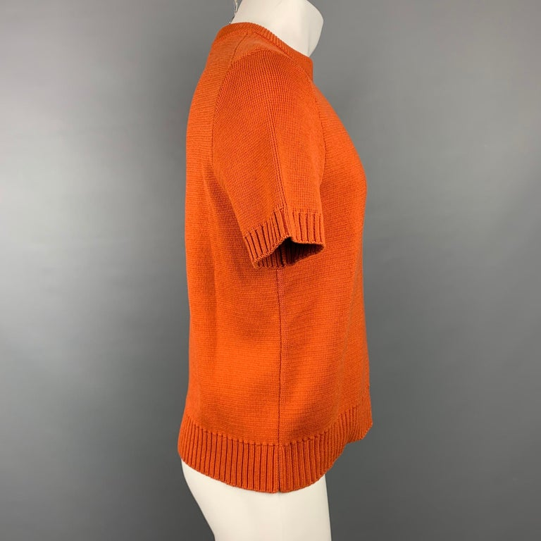 MARNI short sleeve pullover comes in orange knitted cotton featuring a crew-neck. Made in Italy.  Very Good Pre-Owned Condition. Marked: IT 46  Measurements:  Shoulder: 18 in. Chest: 39 in. Sleeve: 10 in. Length: 23.5 in.