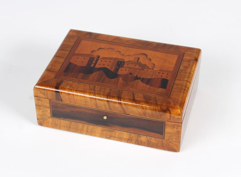 Small wooden box  Germany Walnut and other precious woods Middle of the 20th century.  dimensions: h x w x d: 7 x 19 x 14 cm  Description: Small box with beautiful Marquetry. Inlayed is a scene of a coastal town.  Restored and shellac