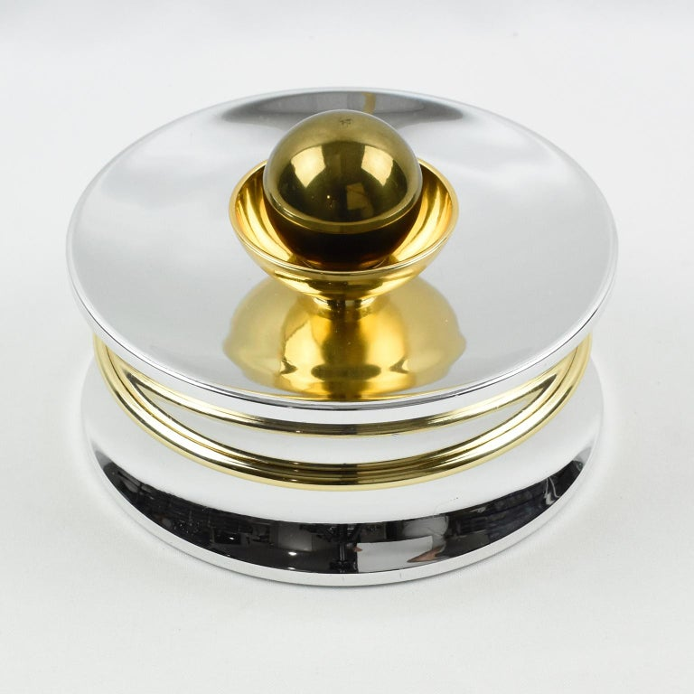 Rare elegant 1970s chrome and brass candy gift box for A La Marquise De Sevigne, finest Paris chocolatier store. Round modernist shape with shiny chromed metal and brass accent and large ball finial. Marked underside with the store logo. This lovely