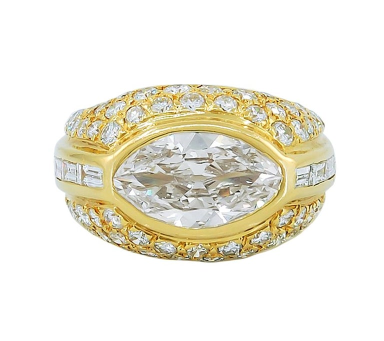 Marquise Diamond Dome Ring in 18k Yellow Gold. A bombé ring featuring a gorgeous marquise-cut diamond bezel-set in east-west form and embellished with round brilliant diamonds. In addition, a channel of straight baguette-cut diamonds frame the