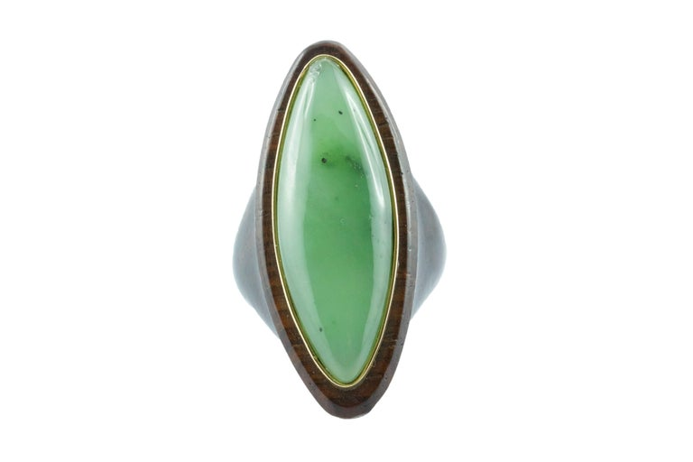 This incredible ring is totally hand-carved not only the stone but also the wood , the jade is shape as marquise and thanks to his vivid green color is an unique piece. The center stone is surrounded by a band in 18k yellow gold and the mounting is