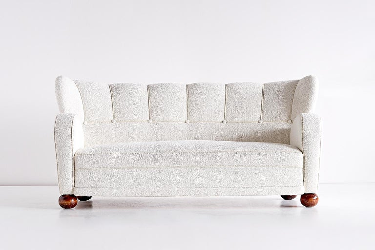 This rare sofa was designed by Märta Blomstedt and produced in Finland in the 1940s. The sofa has been fully reconditioned and newly upholstered in a white bouclé fabric.  One of the driving forces of the Finnish functionalism movement, the