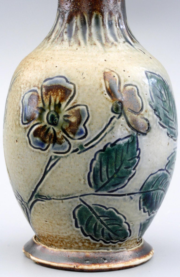 A Martin Brothers stoneware art pottery vase decorated with incised flowering dog roses decorated in brown and blue glazes dating from the 19th century. The small bottle shaped vase stands on a wide rounded foot with a rounded bulbous body and a