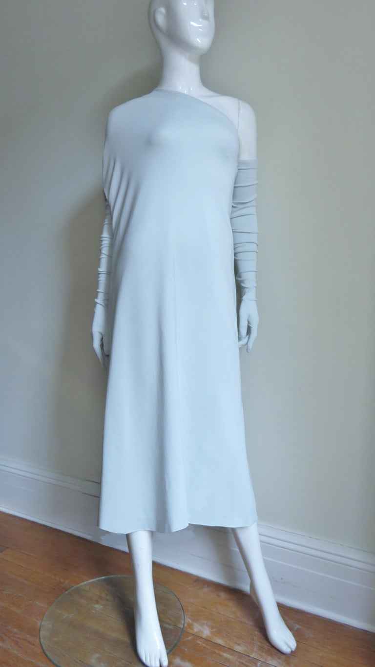 A fabulous dramatic pale mint one shoulder jersey dress from Martin Margiela with matching long gloves.  The dress drapes over one shoulder and has an adjustable zippered opening for the arm to go through which includes a pocket.  The other side