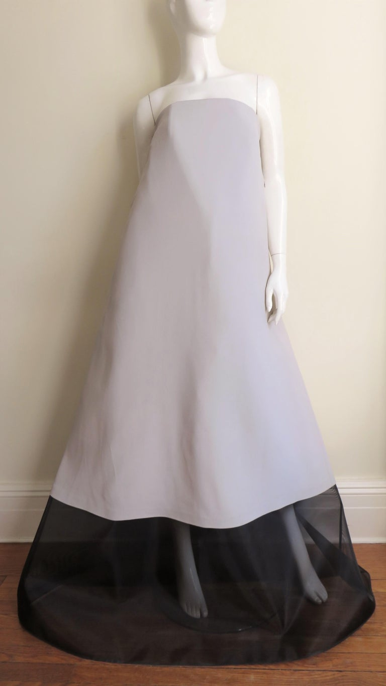 A fabulous light taupe silk and black strapless gown from Martin Margiela top line blank label collection.  It falls in an A line from top to hem- taupe down to the mid calf then black netting around the circumference to the hem.  It has an inner