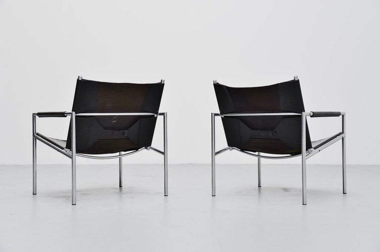 Modernist pair of lounge chairs model SZ01 designed by Martin Visser for 't Spectrum, Holland 1965. These chairs have a brushed steel tubular frame and very thick black saddle leather seats and arm rests finishing, a nice detail is the leather belt