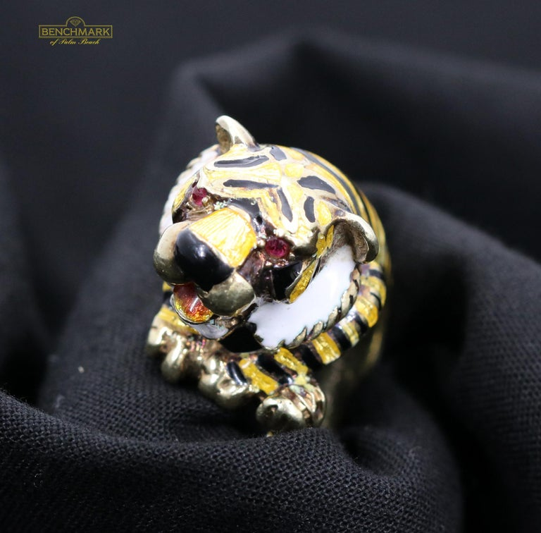 A 14K yellow gold ring with a tiger design, featuring ruby eyes, and beautiful enameled body, stripes, and beard. Measuring 5/8 of an inch wide, this ring comes to life in a size 7. Overall weight is 18 grams.