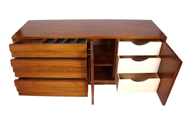 A beautiful Mid-Century Modern walnut dresser designed by Merton Gershun for American of Martinsville with louvered drawers and polished brass drawer pulls. In excellent original condition. The doors on the right open to reveal 3 white front