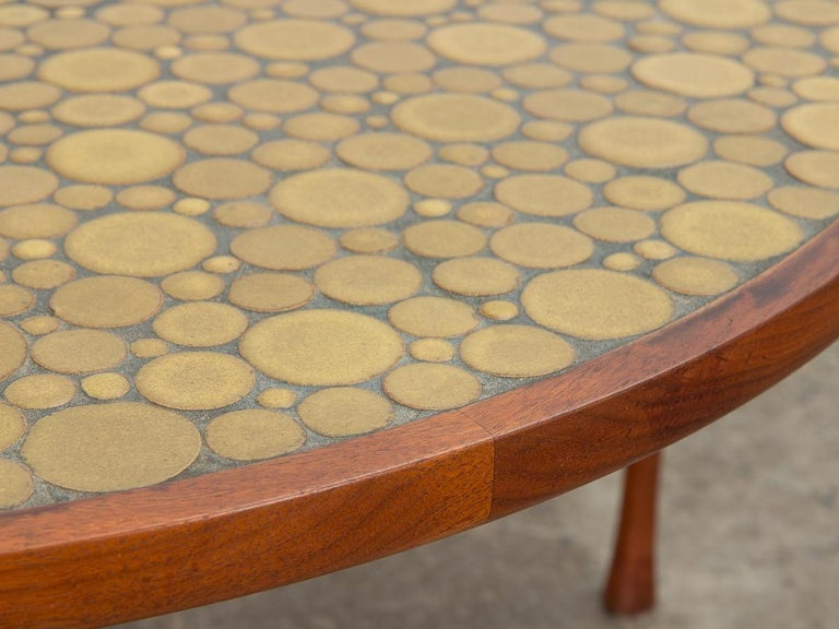 Lovely coin tile top coffee table, designed by Jane and Gordon Martz for Marshall Studio. Signature inlaid ceramic mosaic with deep ochre, yellow ceramic coin tiles. walnut wood form. Gleaming walnut base with playfully flared legs showcases high