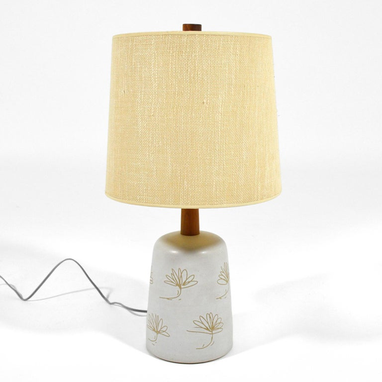 This terrifilc lamp by Gordon and Jane Marts for Marshall Studios features a delicate floral design rendered in sgraffito on the eggshell white glazed base. It retains its original shade and walnut fineal.