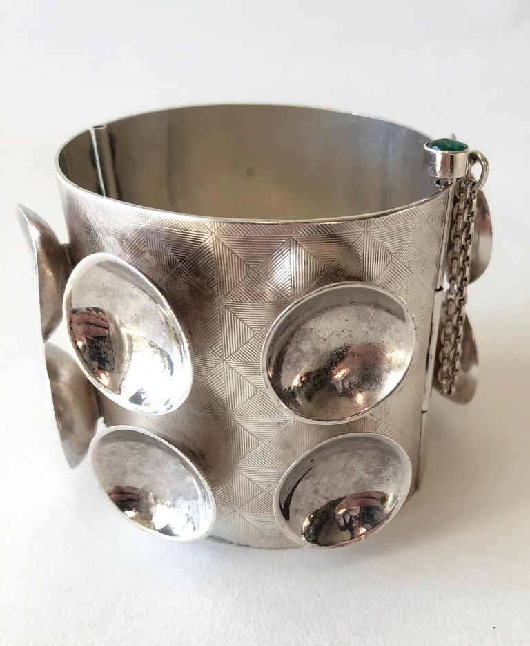 One of a kind sterling silver cuff bracelet decorated with concave cups and incised design by Mary Ann Scherr of North Carolina.  Bracelet fastens with a long pin, which is topped with an emerald cabochon.  Cuff is 2.25