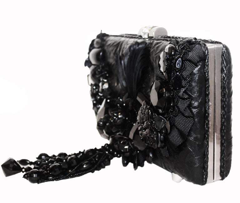 Mary Frances black heavily beaded clutch bag includes a detachable shoulder chain.  This structured leather bag decorated with large plastic, resin and metal ornaments of flowers and butterflies opens to a center compartment lined in black raw silk