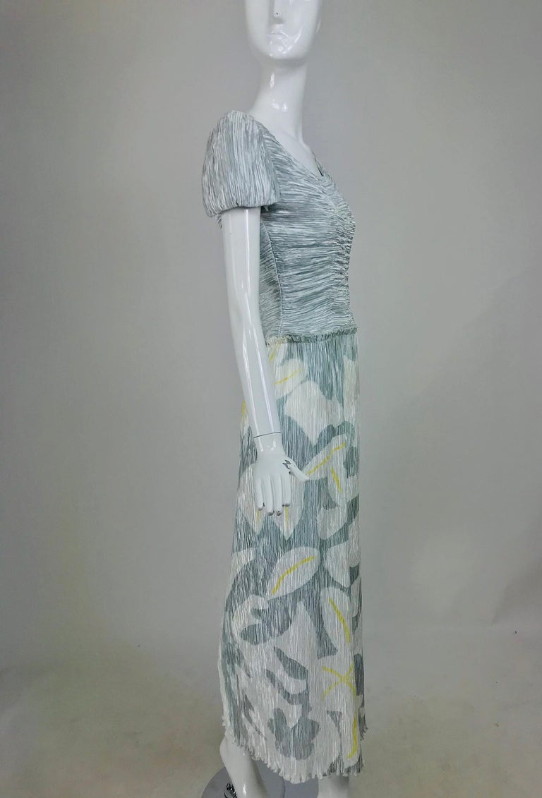 Mary McFadden Couture, pleated and painted evening gown in light and dark silver blue grey, the long pleated skirt has a modernist flower and vine dow the right side, the flowers have yellow centers. The bodice is horizontally pleated with short