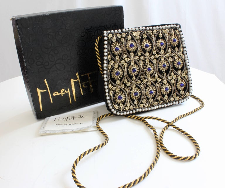 This embellished evening bag was made by Mary McFadden, most likely in the 1980s.  Made from black velvet and satin, the top flap is embellished with gold metallic embroidery and blue cabochons, with a dotting of tiny pearls as a border.  The