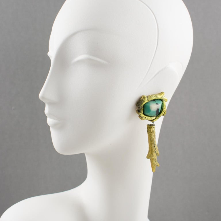 Stunning oversized clip-on earrings, by Mary Oros, made by this Californian artist in the 1980s. Featuring organic feel dangling shape in cast resin with gilt coating topped with turquoise blue, white, and black resin cabochon that almost looks like