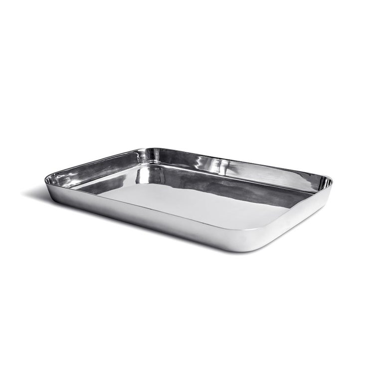 Masai is a family of rectangular polished metal trays designed by Aldo Cibic, available in two different sizes: small and large. The high edges and the rounded corner make this tray an handy object. The large one is perfect, for example, to serve