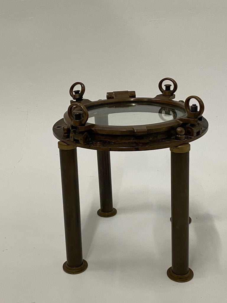 Cleverly designed nautical style end table custom made from an antique brass porthole.