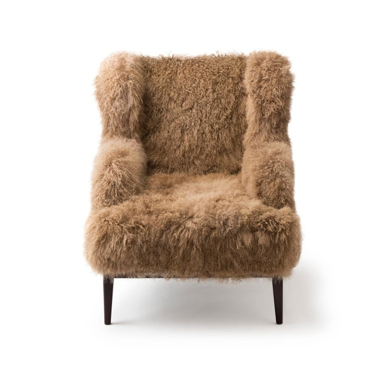 The traditional wingback armchair consists of a stained solid wood structure with a Mongolian lamb seat and back. This armchair is built by hand using traditional methods, the greatest care and the highest quality materials. Dimension: Height 107