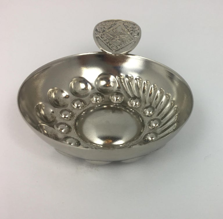 Collection of Masonic keepsakes consisting of two silver round lidded containers and one round silver plated dish/bowl with a handle all showing different symbols of Freemasonry. Lidded containers may have been used to hold a ring, cufflinks, pills